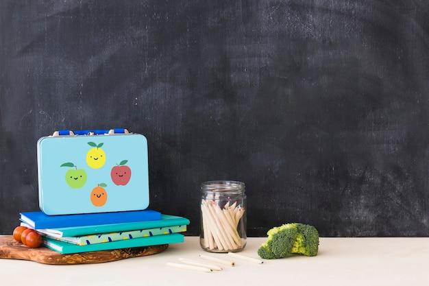 Légumes près de la papeterie et boîte à lunch Photo gratuit