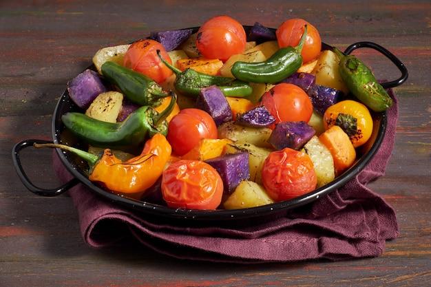 Légumes rustiques cuits au four dans un plat allant au four. repas végétarien de saison sur bois sombre avec une serviette en lin Photo Premium