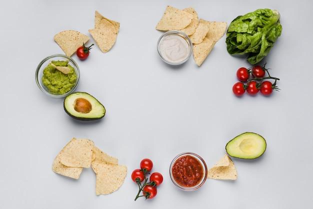 Légumes et sauces dans des bols parmi des tas de nachos Photo gratuit