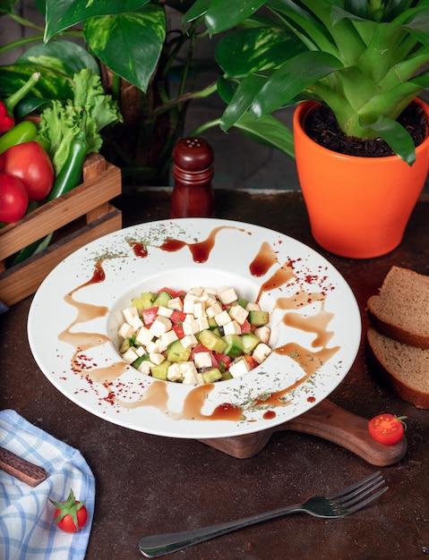 Légumes, tomates, concombre, salade de roka. salade au sumakh et au citron sur la table de la cuisine à l'intérieur de la plaque blanche Photo gratuit