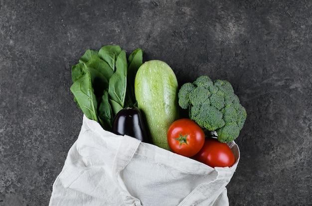 Légumes végétaliens dans un sac réutilisable de cotoon sur une table en ardoise foncée. zéro déchet, soins, concept santé Photo Premium