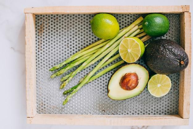 Légumes verts en bonne santé dans une boîte en bois sur fond de marbre blanc, vue de dessus Photo Premium