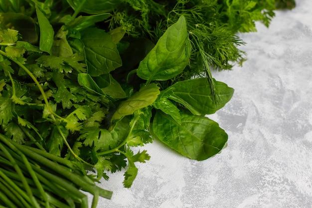 Légumes verts frais, coriandre, laitue, basilic pourpre, coriandre de montagne, aneth, oignon vert dans des boîtes en plastique recouvertes de béton gris Photo gratuit