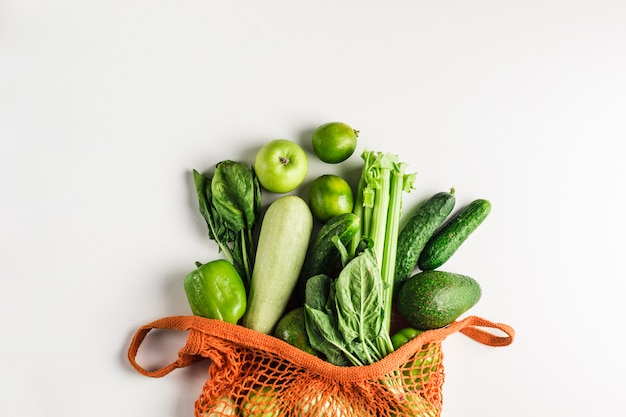 Légumes verts et fruits dans un sac orange Photo Premium