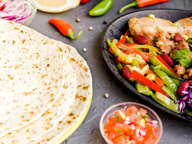 Légumes et viande à côté des tortillas Photo gratuit