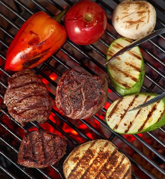 Légumes Et Viande Grésillant Sur Le Gril Avec Des Flammes, Gros Plan Photo Premium