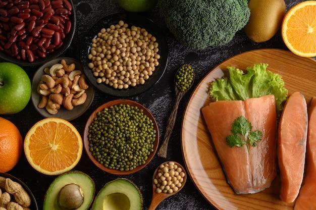 Légumineuses, Fruits Et Morceaux De Saumon Sur Une Plaque En Bois. Photo gratuit