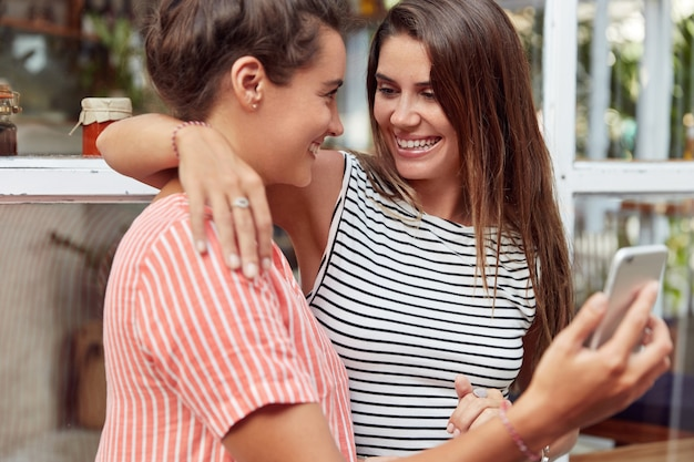 Les Lesbiennes Joyeuses S'embrassent Passionnément Et S'amusent Ensemble, Utilisent Un Téléphone Portable Moderne Pour Faire Des Photos Ou Se Divertir, Démontrent Des Relations Homosexuelles. Un Couple De Samesex Utilise Un Appareil électronique Photo gratuit
