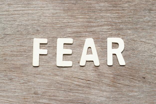 Lettre de l'alphabet dans le mot peur sur fond de bois Photo Premium