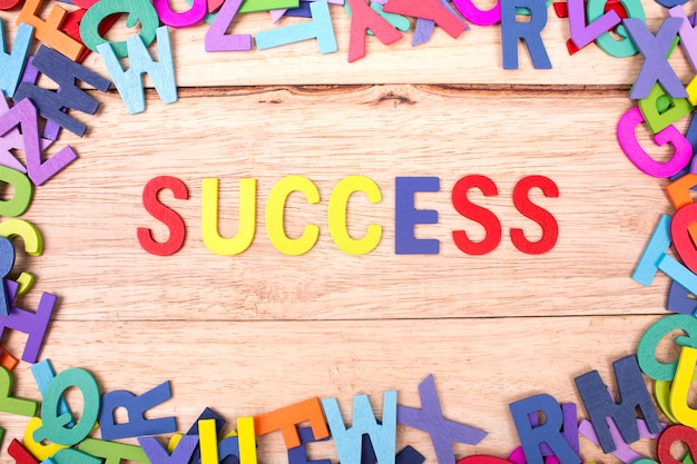Lettre en bois colorée de l'alphabet et du mot succès isolé sur fond de bois Photo Premium