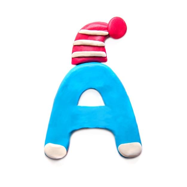 Lettre De Pâte à Modeler Bleu A De L'alphabet En Hiver Chapeau Rouge Sur Fond Blanc Photo Premium