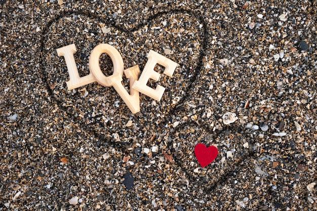 Lettres En Bois Formant Le Mot Amour Avec Un Coeur Rouge Sur Le Sable De La Plage, à L'intérieur D'un Coeur Fait Avec Les Doigts. Concept De San Valentine Photo Premium