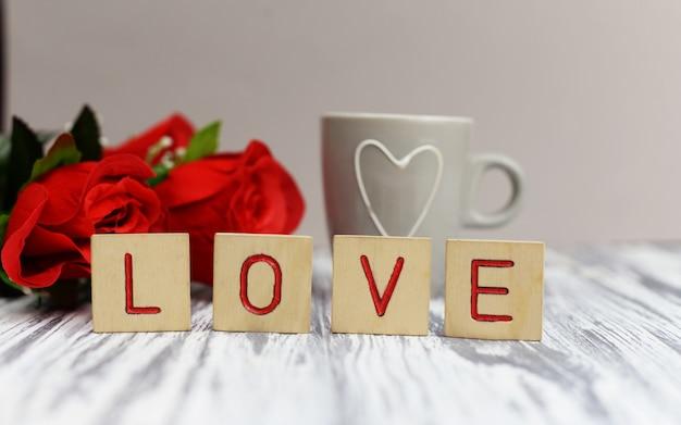 Lettres en bois lettrage texte amour fleurs rouges Photo Premium
