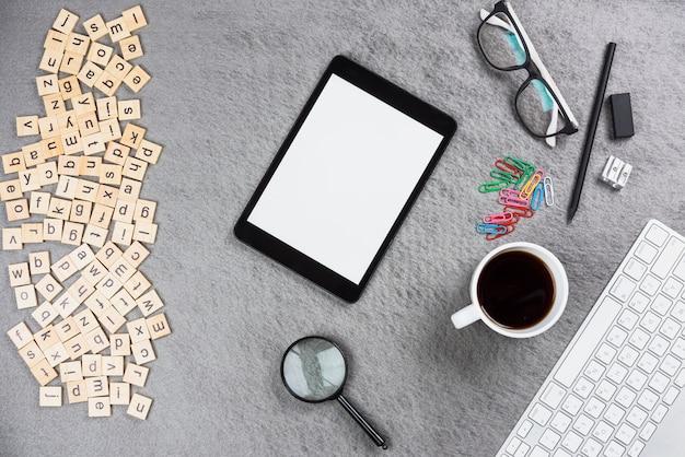 Lettres en bois; tablette numérique; tasse à café et fournitures de bureau sur fond gris Photo gratuit