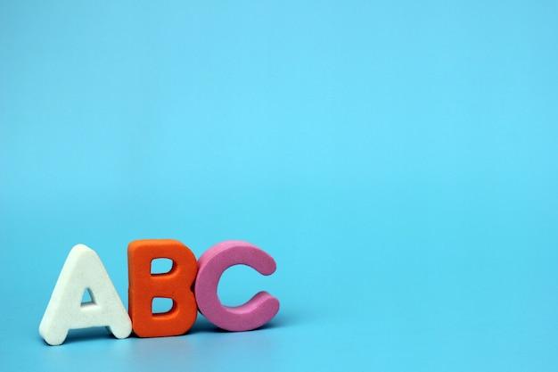 Les Lettres De Couleur De L'abc Sont Isolées Sur Un Fond Bleu Photo Premium