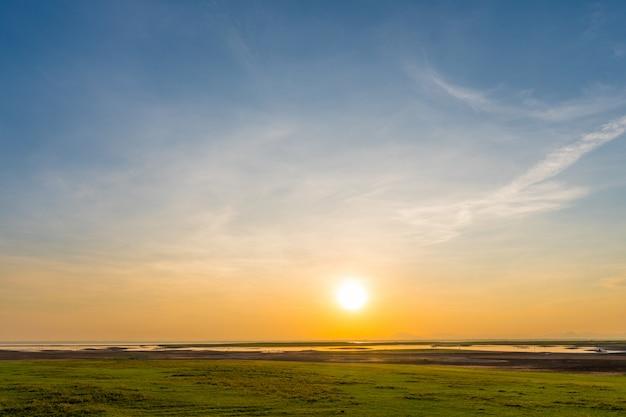 Lever du soleil au bord du lac avec pelouse verte et ciel bleu Photo Premium