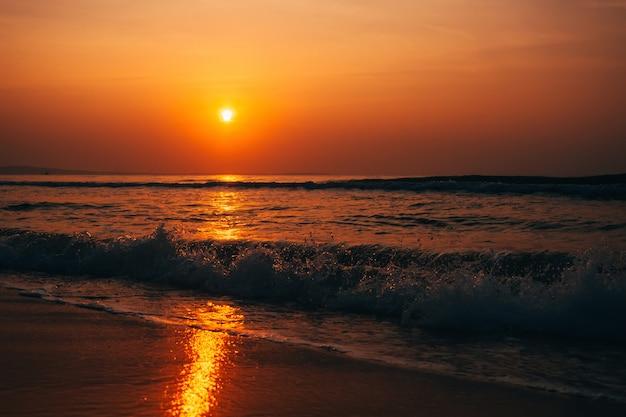 Lever du soleil orange sur la mer avec des vagues en été Photo Premium
