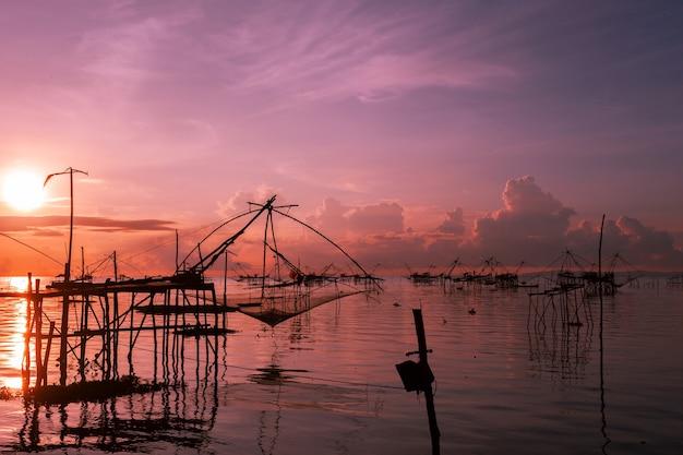 Lever du soleil avec un piège de pêche dans le village de pak pra, phatthalung, thaïlande Photo Premium