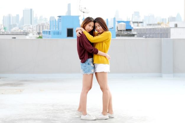 Lgbt, jeune couple de lesbiennes asiatiques mignon étreindre et souriant avec bonheur sur leur rencontre Photo Premium