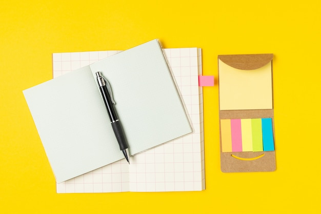 Lieu de travail, bloc-notes, notes autocollantes et stylo sur jaune vif Photo Premium
