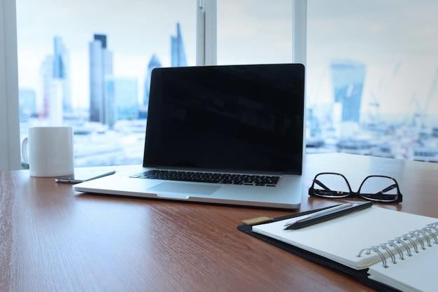 Lieu de travail de bureau avec ordinateur portable à écran blanc et téléphone intelligent sur une table en bois Photo Premium