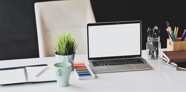 Lieu de travail de concepteur avec ordinateur portable à écran blanc et fournitures de bureau Photo Premium