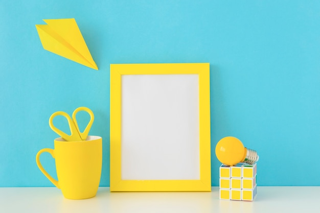 Lieu de travail créatif aux couleurs bleues et jaunes avec cube et ampoule de rubik Photo gratuit