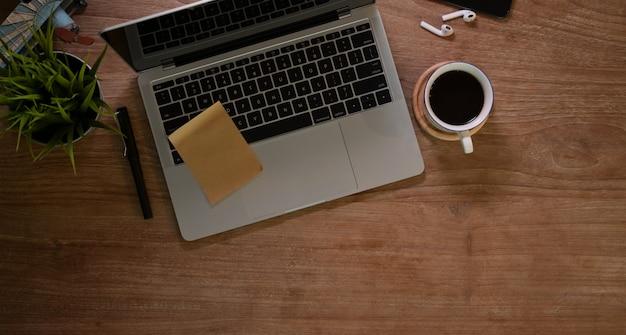 Lieu de travail de designer rustique avec un ordinateur portable et une tasse de café Photo Premium
