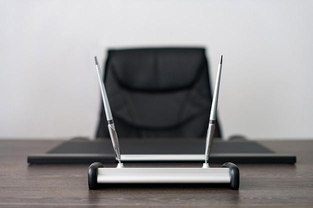 Lieu de travail du chef d'entreprise: fauteuil en cuir, instruments d'écriture. Photo Premium