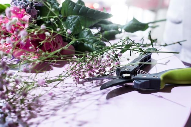 Le Lieu De Travail Du Fleuriste Est Une Table Avec Des Fleurs Et Un Sécateur Photo Premium
