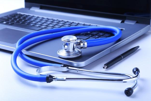 Lieu de travail du médecin avec ordinateur portable, stéthoscope et prescription rx sur une table blanche Photo Premium