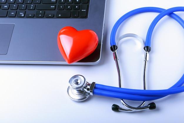 Lieu de travail du médecin avec stéthoscope, coeur rouge, ordinateur portable, prescription rx et cahier sur tableau blanc Photo Premium