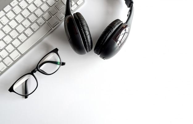 Lieu de travail avec espace de texte, ordinateur à clavier et casque sur la table. sur la lumière Photo Premium