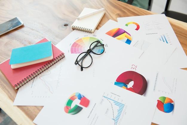 Lieu de travail homme d'affaires avec graphique, cahier de lunettes et un stylo sur le bureau en bois. Photo Premium