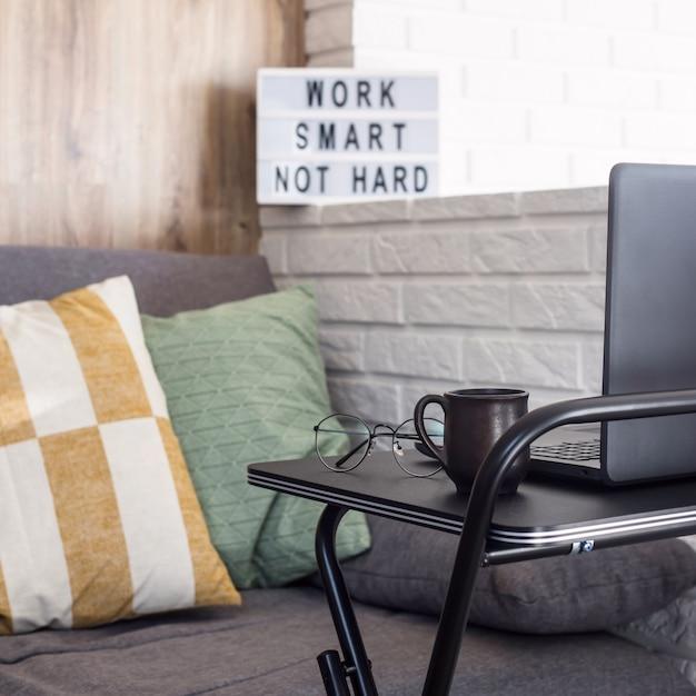 Lieu de travail à la maison d'un pigiste à une table élégante noire près du canapé et du mur de briques Photo Premium