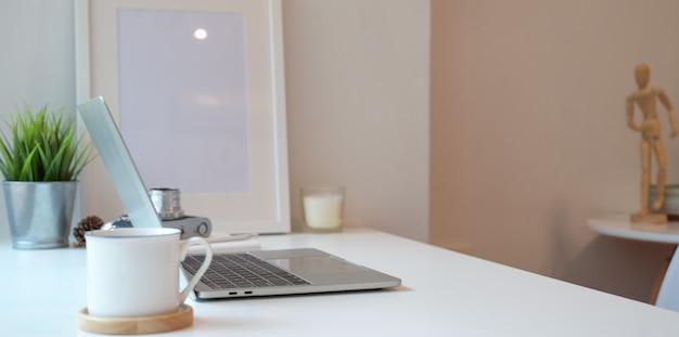 Lieu de travail minimal avec un ordinateur portable et une tasse de café Photo Premium