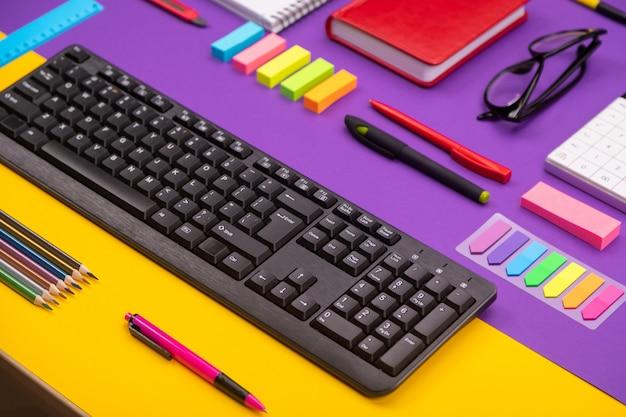 Lieu De Travail Moderne Avec Clavier, Agenda, Crayons, Stylos Et Lunettes Orange-violet. Photo Premium