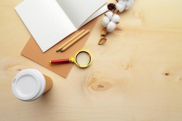 Lieu de travail moderne de couleur beige sur une table en bois avec beaucoup de choses dessus. vue de dessus Photo Premium