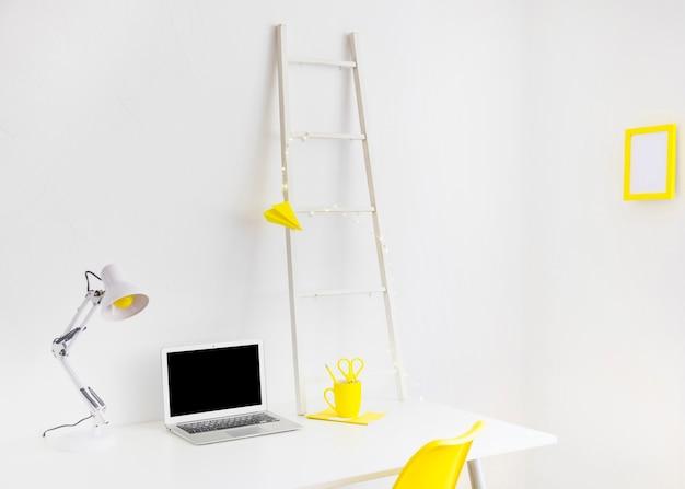 Lieu de travail moderne en couleurs blanches et jaunes avec cadre photo Photo gratuit