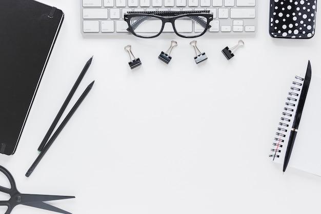 Lieu de travail avec papeterie et lunettes sur clavier Photo gratuit