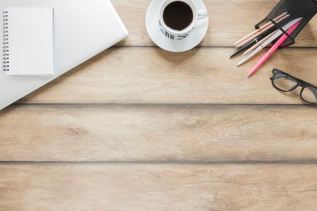 Lieu de travail avec papeterie, ordinateur portable et tasse de café Photo gratuit