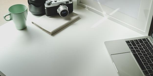 Lieu de travail de photographe à la mode avec tablette et appareil photo vintage Photo Premium