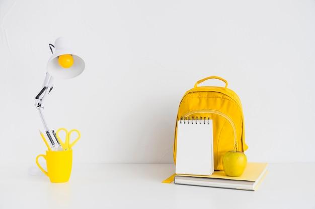 Lieu de travail avec sac à dos jaune et pomme Photo gratuit