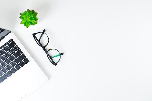 Lieux de travail modernes avec ordinateurs portables, lunettes et petits arbres avec espace de copie sur fond blanc. vue de dessus. Photo Premium