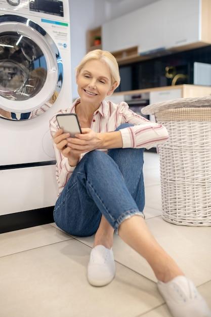 En Ligne. Femme Au Foyer Blonde En Chemise Rayée Assis Près De La Machine à Laver Et Lire Quelque Chose En Ligne Photo Premium