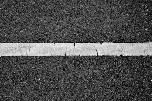 Ligne de peinture blanche sur asphalte noir. fond de transport spatial Photo Premium
