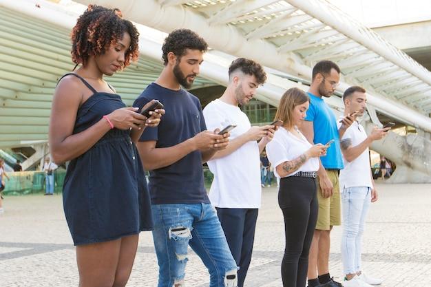 Ligne de personnes naviguant sur internet avec un smartphone à l'extérieur Photo gratuit