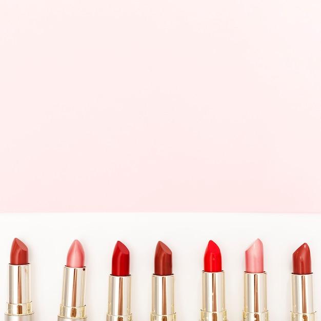Ligne de rouges à lèvres métalliques sur fond blanc Photo gratuit