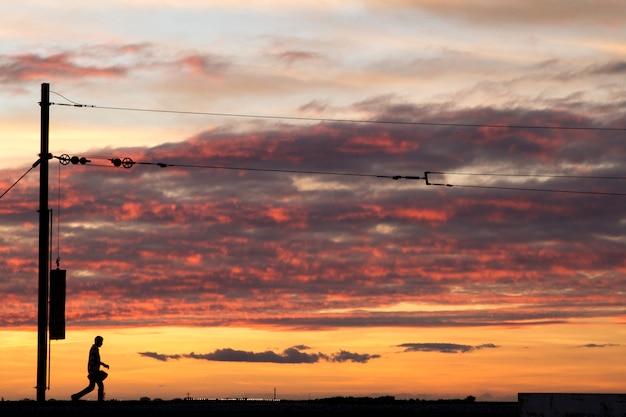 Des lignes de chemin de fer filent contre un ciel nuageux en fin de journée. Photo Premium