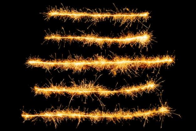 Lignes de feux d'artifice étincelles isolées sur fond noir. Photo Premium